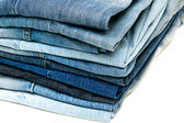 Stack of blue jeans on white background — Stock Photo