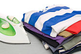 Stack of colorful clothes and electric iron — Stock Photo