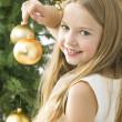 Smiling girl with christmas balls next to green tree — Stock Photo