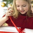 Beautiful teenage girl opening her christmas present. Christmas — Stock Photo