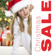 Young blonde girl in santa hat and red comforter behind white bo — Stock Photo #7894860