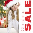 Stock Photo: Young blonde girl in santa hat and red comforter behind white bo