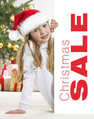 Young blonde girl in santa hat and red comforter behind white bo — Stock Photo