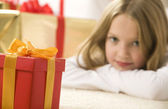 Pretty blonde hair girl looking at small red gift with gold ribb — ストック写真