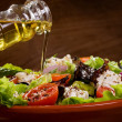 Stock Photo: Vegetable salad with olive oil pouring from bottle