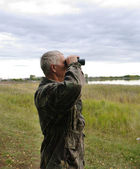 Man looks in binoculars мужчина смотрит в бинокль — Stock Photo