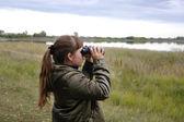 Girl looks in binoculars девочка смотрит в бинокль — Stock Photo