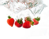 Strawberries dropped into water splash — Stock Photo