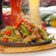 Stock Photo: Original fajitsizzling hot on iron plate