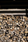 Firewood arranged by the country cottage — Stock Photo