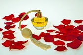 Flacon of perfume in red petals of roses — Stock Photo