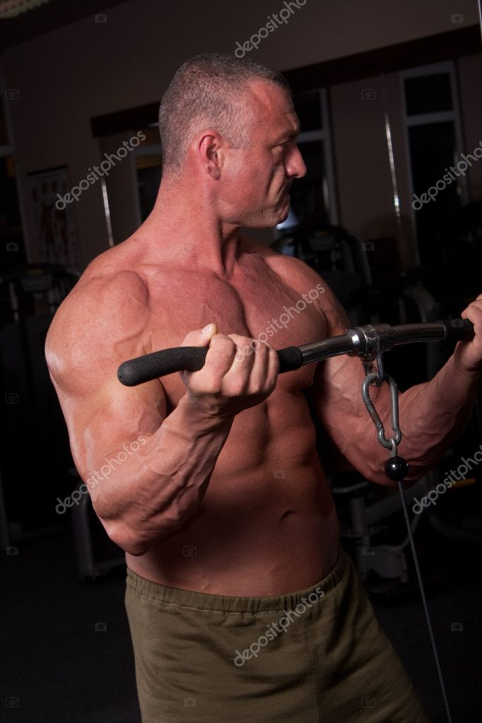 Bodybuilder exercising in a gym  Stock Photo #6888425