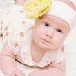 Little cute baby girl with flower on her head — Stock Photo #7038728