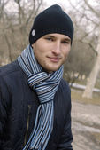 Portrait of young man in black cap and striped scarf — Stock Photo