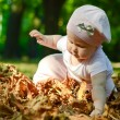 Baby girl in red leaves — Stock Photo