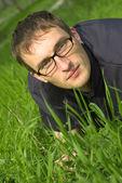 Jonge man in glazen is liyng in groene gras — Stockfoto