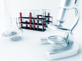 Microscope and glass test tubes — Stock Photo