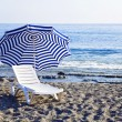 Chaise lounge with an umbrella — Stock Photo