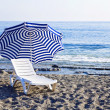 Chaise lounge with an umbrella — Stock Photo #7656057
