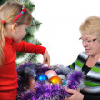 Grandmother with the grand daughter decorate a Christmas tree — Stock Photo #6955179