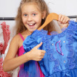 Little girl in shop of dresses and hand shows sign OK — Stock Photo