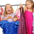 Royalty-Free Stock Photo: Little girls in shop of dresses. Isolated on white