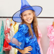 Little girl in shop of dresses tries on a costume of a witch — Stock Photo