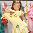 Little girl in shop of dresses — Stock Photo