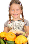 Little girl counts money and vegetables isolated on the white — Stock Photo