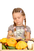 Sad little girl counts money and vegetables isolated on the whit — Stock Photo