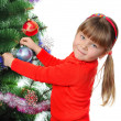 Girl decorates a fur-tree. Isolated on the white — Stock Photo