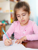 Schoolgirl works on her homework, writes on paper — Stock Photo