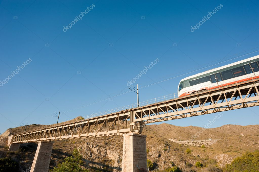 A small narrow gauge train crossing a bridge — Stock Photo #7456885