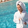 Stock Photo: Girl in a white coat at the outdoor swimming pool