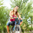 Couple on a bike outdoor smiling — Stock Photo