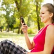 Woman with mobile phone in park — Stock Photo