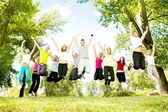 Large group of teens jumping together — Stock Photo
