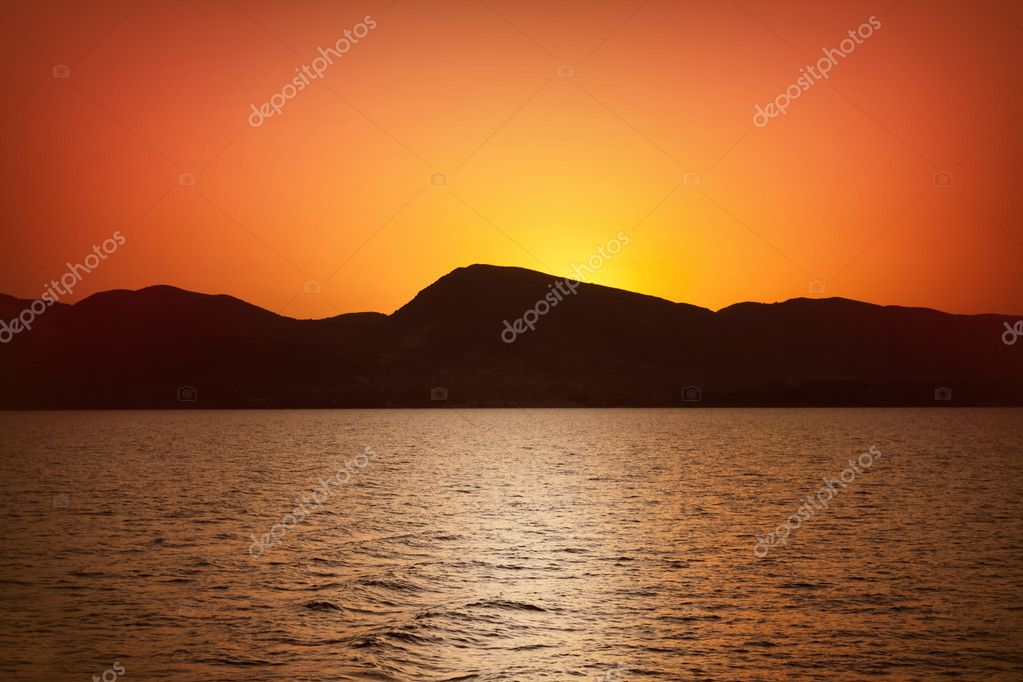 Sunset landscape - sea, mountains, yellow sky — Stock Photo #6836451