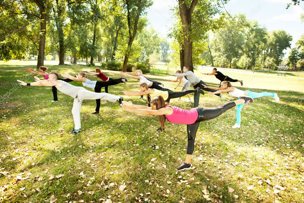 Group of young  in park doing aerobics or warming up with gymnastics and stretching exercises — Stock Photo #6836875
