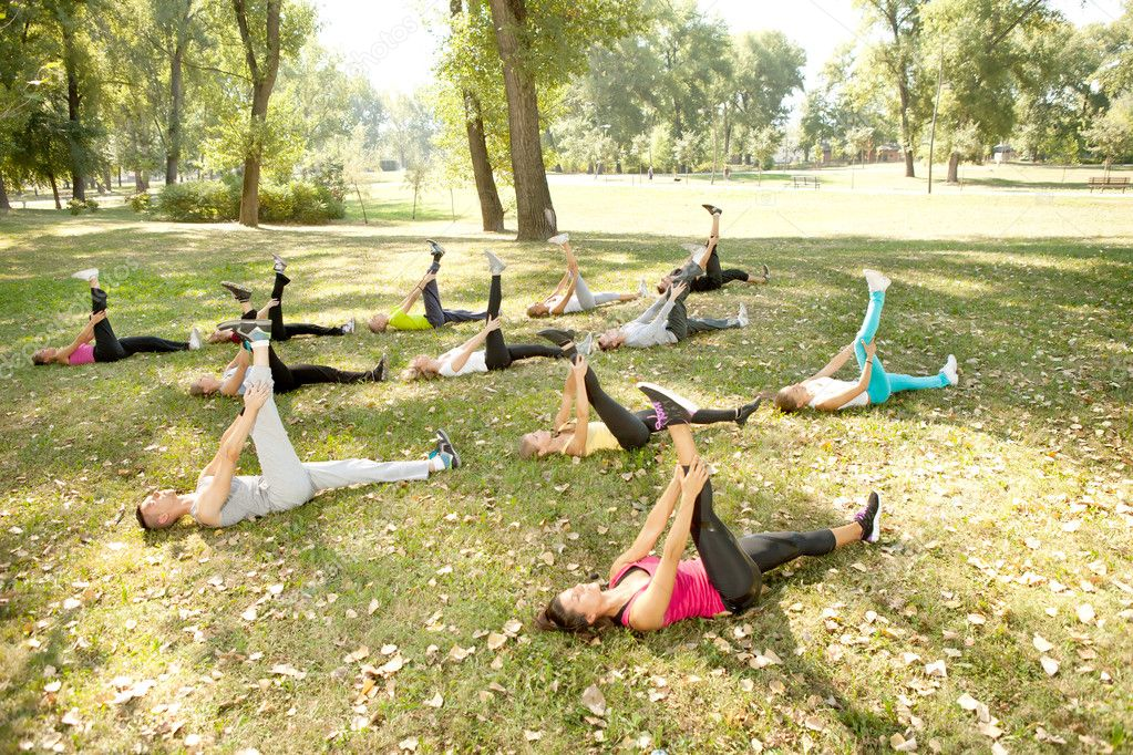 Large group of lying on grass and stretching, outdoor — Stock Photo #6916037