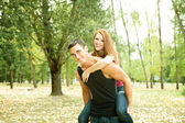 Couple playing piggyback — Stockfoto