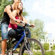 Love couple riding a bicycle in a park — Stock Photo