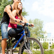 Stock Photo: Love couple riding a bicycle in a park