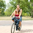 Happy couple riding on a bicycle — Stock Photo