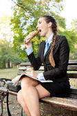 Hungry businesswoman in park — Stock Photo