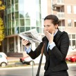 Worried businesswoman reading newspaper — Stock Photo