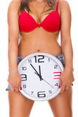 Naked woman holding clock — Stock Photo