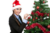 Girl decorate a christmas tree — Stock Photo