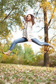 Girl jumping in autumn park — Stock Photo
