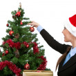 Decorating christmas tree - Stock Photo